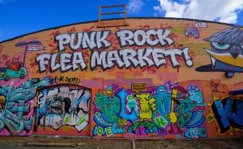 "Photo depicting a giant street-art mural that reads ""Punk Rock Flea Market."""