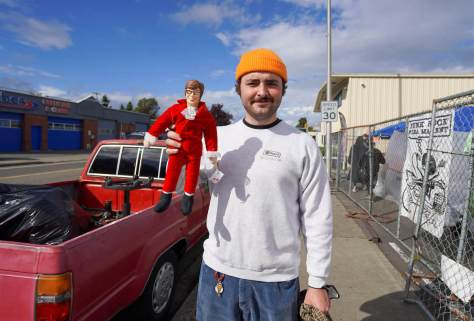 Photo depicting a male-presenting individual with an orange beanie holding out an Austin Powers figurine wearing its iconic red suit.