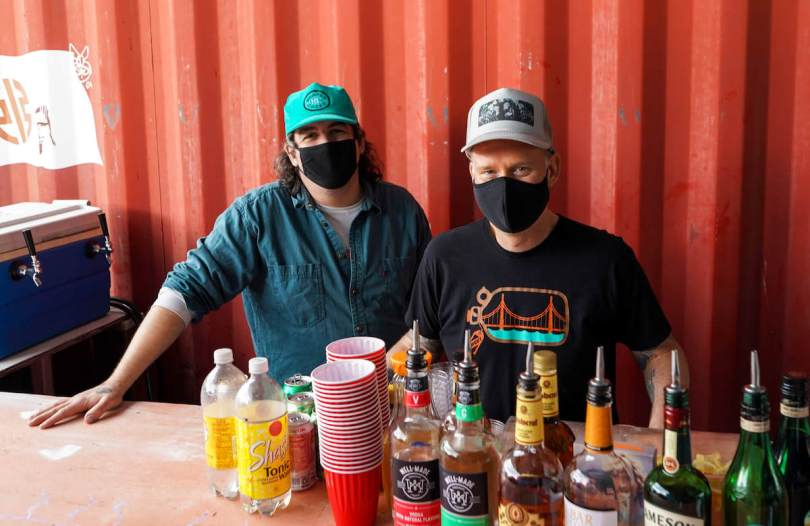 Photo depicting two male-presenting individuals with black face masks standing behind a bar with various spirits.