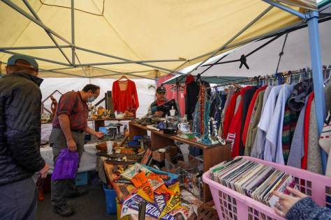 Photo depicting customers browsing various wares at an outdoor flea market booth.