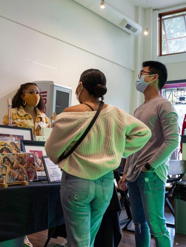 Photo depicting Stephanie Morales with a mustard-yellow surgical mask standing behind her booth featuring artwork speaking to event attendees