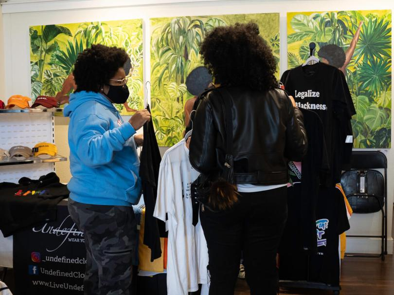 Photo depicting two Black-presenting individuals browsing through clothing at a booth at The Liink Project