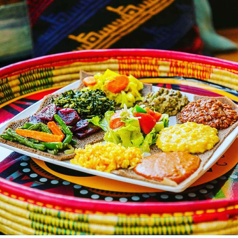 Photo depicting a brightly colored Ethiopian dish of vegetables and spices served on top of injera, a spongy flatbread. The dish rests on a brightly colored woven basket.