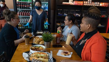 Photo depicting a group of female-presenting individuals eating at a table filled with delicious food at Le's Deli and Bakery. A female-presenting restauranteur checks in on them.