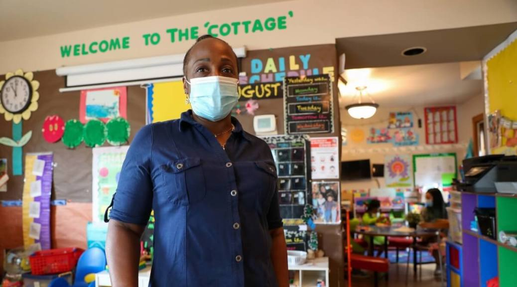 """A Black woman in a blue button-up shirt stands in a classroom. A sign above her reads """"Welcome to the 'cottage'"""""""