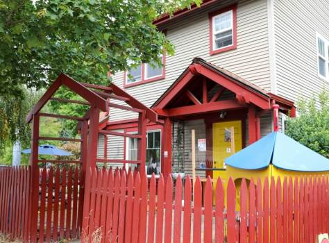 An off-white house with red trim and a yellow door surrounded by a red picket fence. A play house in yellow and blue stands in the yard.