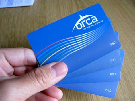 Photo depicting a hand holding four blue ORCA cards against a wood-grained background.