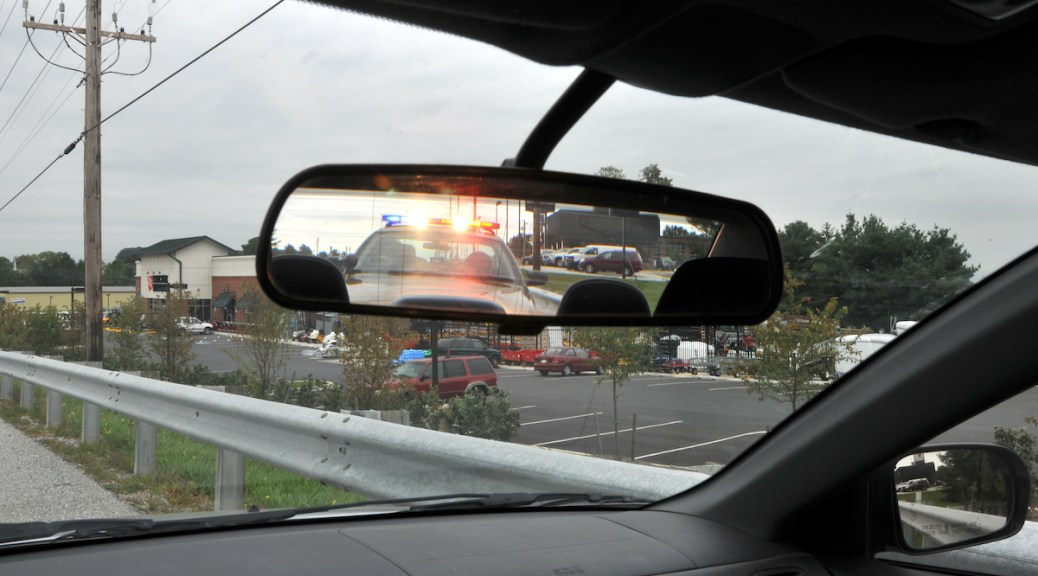 Photo depicting the rear-view mirror in a car where a police car with flashing lights is reflected in the mirror.