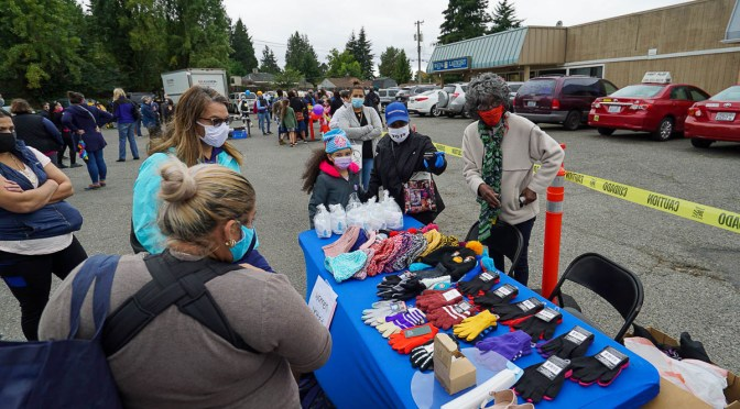 Photo depicting individuals gathered around a table handing out mittens at the 2020 pop-up resource center in Skyway.
