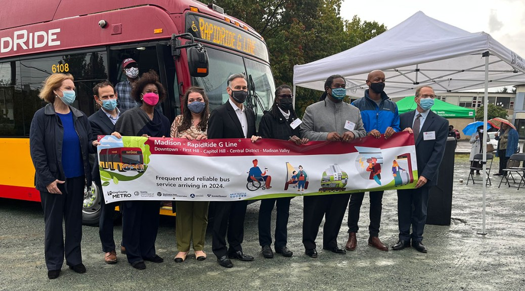 Photo depicting local officials holding a banner announcing the RapidRide G Line expansion project. A RapidRide G Line bus stands behind the officials.