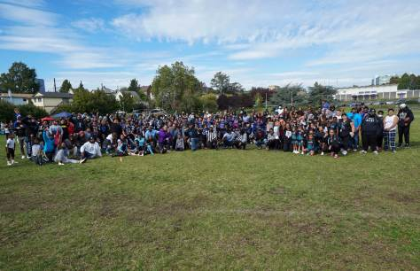 Photo depicting a large gathering of friends, family, and community members on Judkins Park's football field.