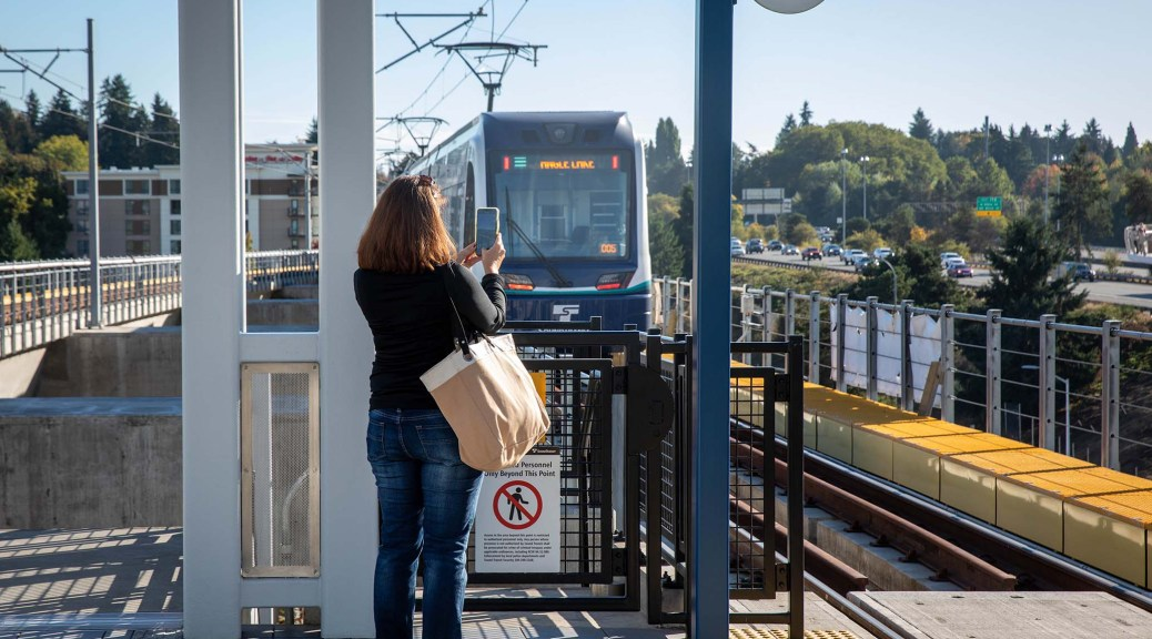 Photo depicting the upper level of the Northgate Station. A female-presenting individual takes a photo with their cell phone as the train pulls in.
