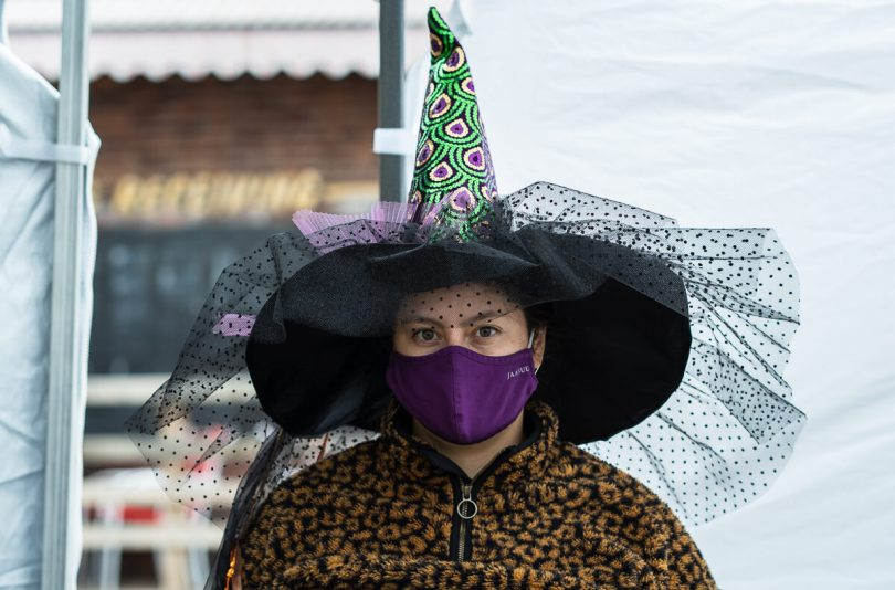 Photo depicting Heidi Khrone in a green and purple witch hat and a purple surgical face mask.