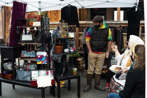 A customer browses through Moda Boscolo's vendor station of unique items.