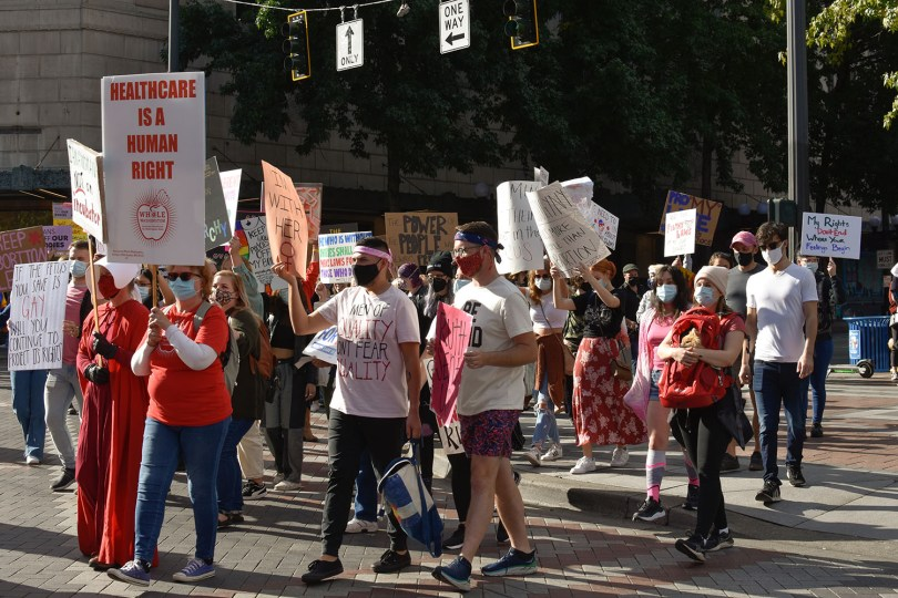 Photo depicting a group of protestors marching with protest signs advocating for reproductive justice.