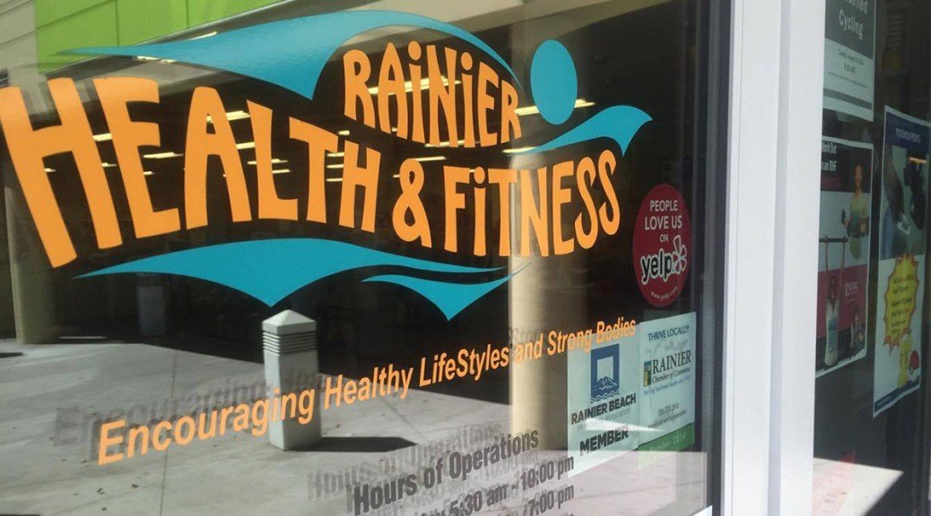 """Photo depicting an exterior window with bright-orange text that reads """"Rainier Health & Fitness"""""""