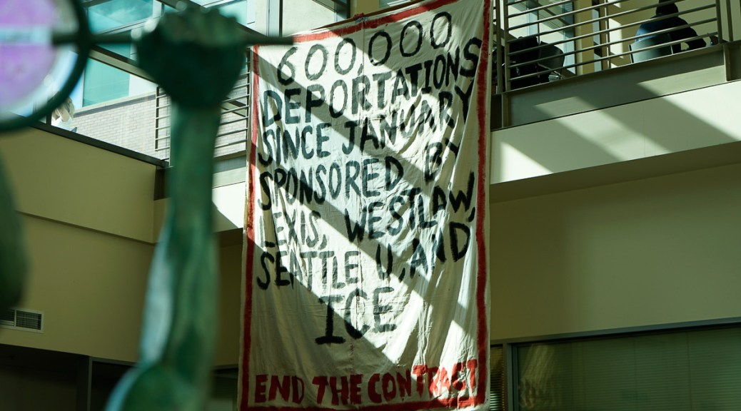 """Photo depicting a banner hung over a railing that reads """"600,000 deportations since January sponsored by Lexis, Westlaw, Seattle U, and ICE. End the Contract."""""""