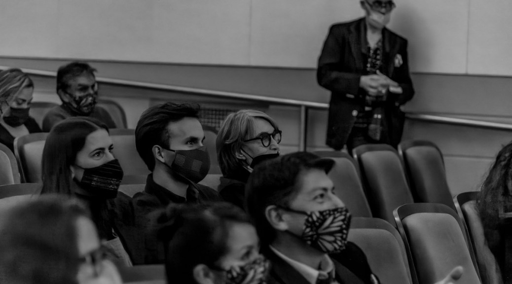 Black-and-white photo depicting a crowd of theater attendees with face masks seated in a movie theater.