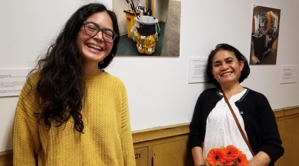 Art exhibit curator Evalynn Fae Taggana Romano, left, and her mother, Evalina Taggana Romano, at the exhibit hanging in a hallway of the Art Building at the University of Washington. Custodian Romano cleans this hall every day. (Photo: Sally James)