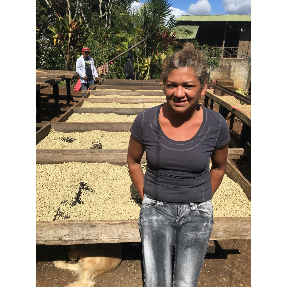 Photo of farmer Maria Velazquez posing in front of her coffee drying on raised beds at her farm in Jinotega Nicaragua