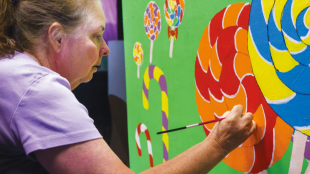 STAGE MAGIC Janelle Cummings painting lollipops for the chocolate smelting room in South Valley Civic Theater's production of Willy Wonka, opening June 23.