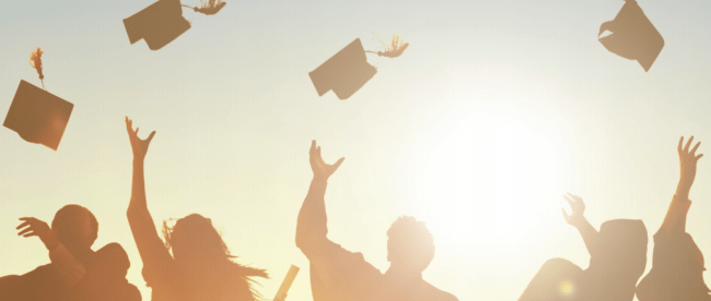 silhouetted graduates throwing up caps into sunset