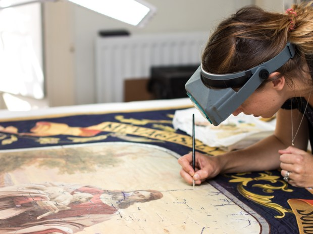 Conservator working on a image depicting Christ. She is using a fine paintbrush and is wearing a light on her head.