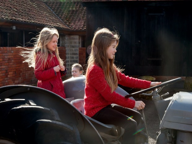Two girls playing on a tractor
