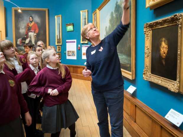 museum member of staff points at an artwork on a gallery wall while a group of children look up at it.