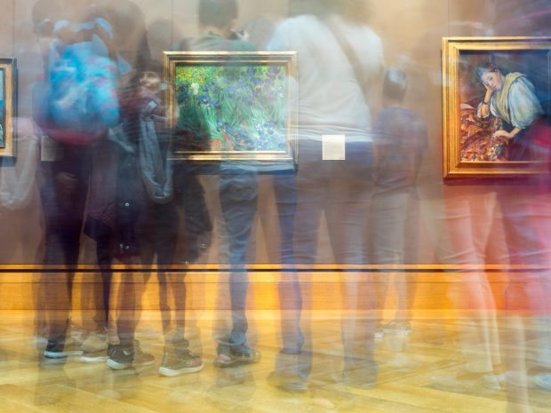 Long exposure image of many people standing in front of paintings in a gallery