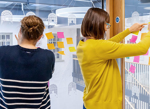 Two women stick post it notes on windows