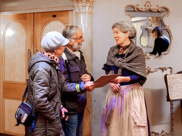 A volunteer in period clothing talks to some visitors
