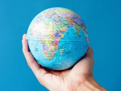A hand holds a small planet earth globe