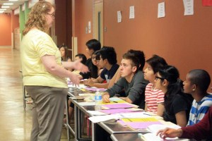 AP World History teacher Ms. Krista Boivie, explains how the IES projects should be graded. AP World History students assessed the regular and honors World History student's projects.<br>Photo Credit: June Gabriel Santos