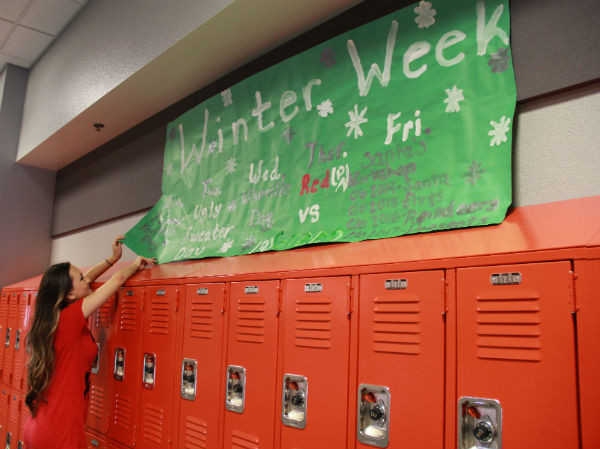 "Senior Alexis Lane adjusts the ""Winter Week"" banner for students to see easily while walking down the hallways. ""Student Council spent a lot of time making the banner, so hopefully people will read them and know what to dress up for,"" Lane said.  Photo Credit: Jen Chiang"