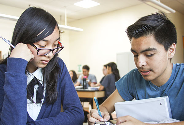 "Sophomores Ricardo Torres and Dyann Mones complete a stoichiometry worksheet in chemistry class on Feb. 19. They will be reviewing for the assessment during class. ""Stoichiometry isn't the bad. I'm getting the hang of it,"" Torres said.  Photo Credit: Migi Contreras"