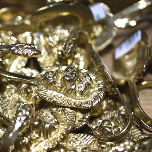 A beguiling pile of gold lion hooks. Souvenir from Vasa Museum Gift Shop, Stockholm, Sweden.