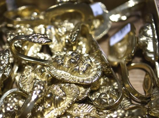 A beguiling pile of gold lion hooks. Souvenir from Vasa Museum Gift Shop, Stockholm, Sweden.