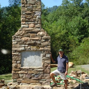 Larry Lamb with the chimney that is a central part of the Memorial. Photo courtesy of Larry Lamb