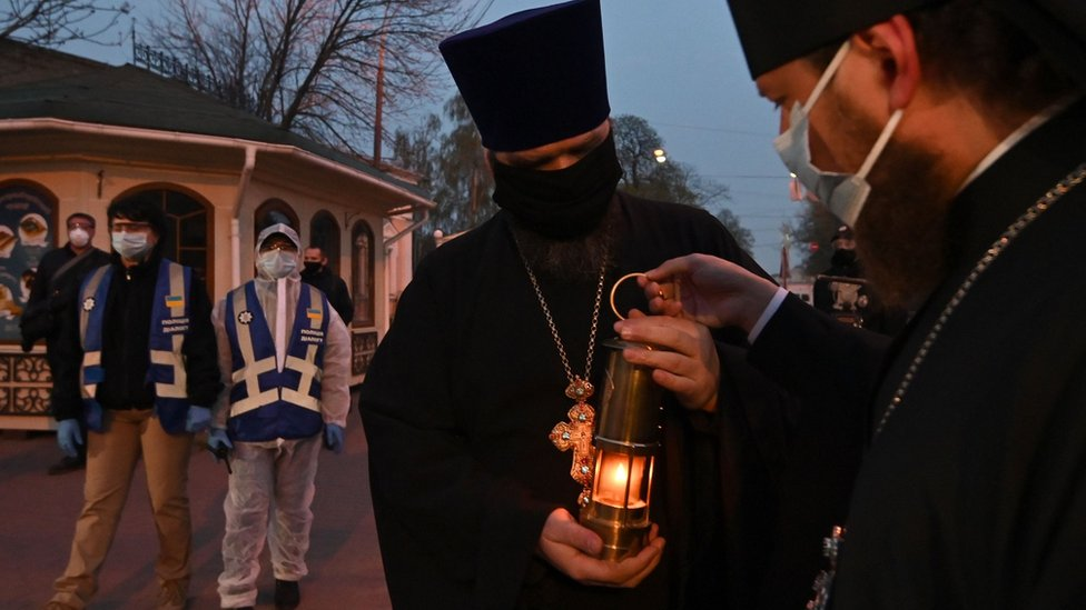 Ukrainian Orthodox priests wearing masks hold a candle with the Holy Fire brought from Jerusalem next to Kiev-Pechersk Lavra monastery in Kiev on April 18, 2020 on the eve of the Orthodox Easter. -