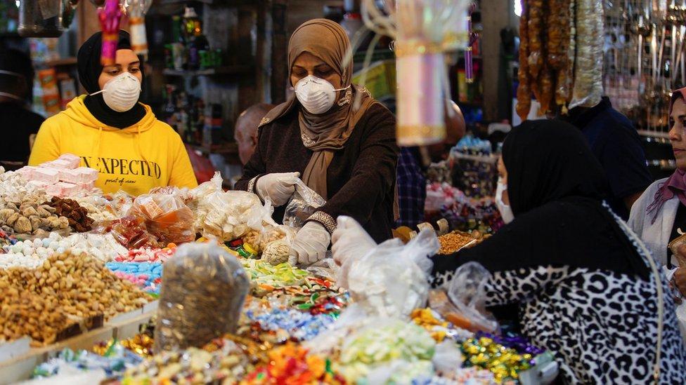 женщины в масках на рынке в багдаде