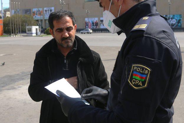 Полицейский в Баку проверяет прохожего