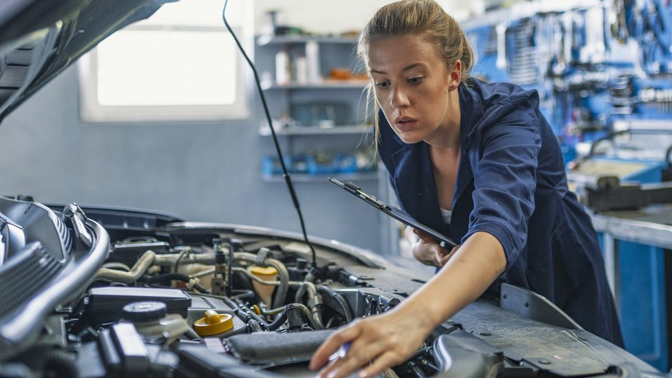 Woman looking at a car engine
