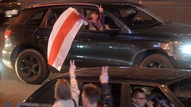 Люди в машине с бело-красно-белым флагом в Минске 23 сентября