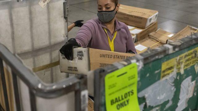 Работница почты разгружает ящики с почтовыми бюллетенями