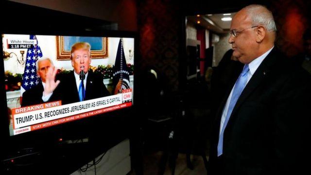 Saeb Erekat staring at Donald Trump on a screen
