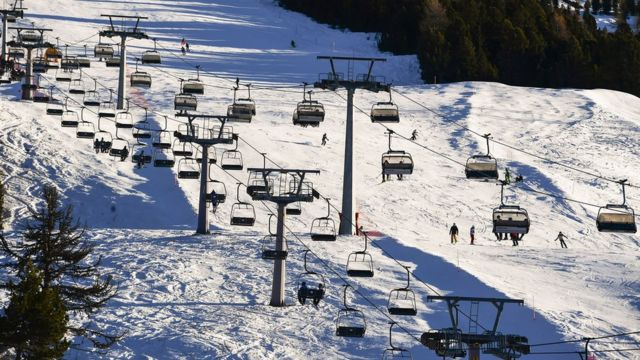 Tourists take chairlifts and enjoy skiing in the Stelvio National Park resort in Bormio, Italian Alps