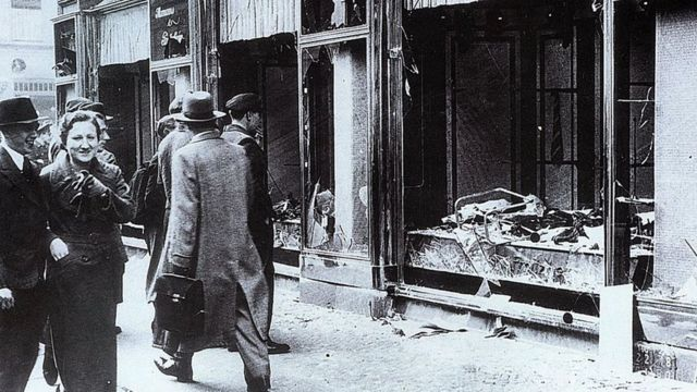 Pedestrians glance at the broken windows of a Jewish owned shop in Berlin after the attacks of Kristallnacht, November 1938.