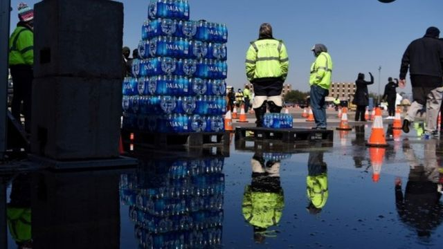 Workers in Houston pass out cases of water