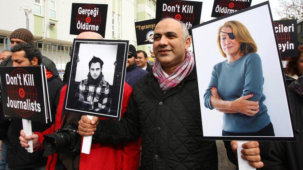 Турецкий журналист держит в руках фотографии журналистов Реми Ошлик и Мари Колвин, убитых в Хомсе 22 февраля 2012 года